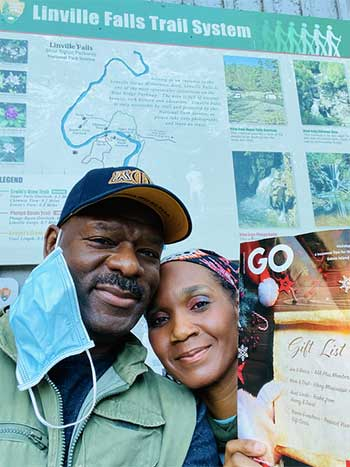 Gowithgo winning photo of a couple with their Go Magazine standing in front of a sign