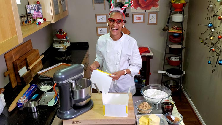 Chef Carla Hall in a kitchen getting ready to cook