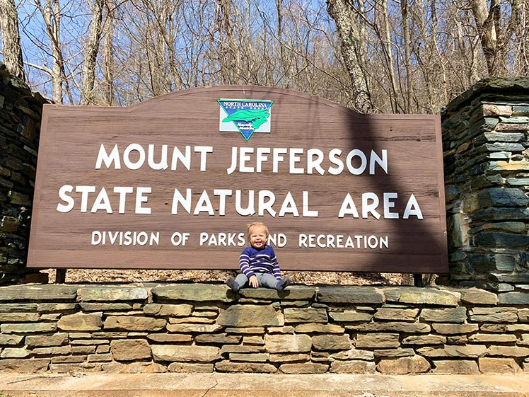 Youngest member of Bartos family poses at theMount Jefferson State National Area sign