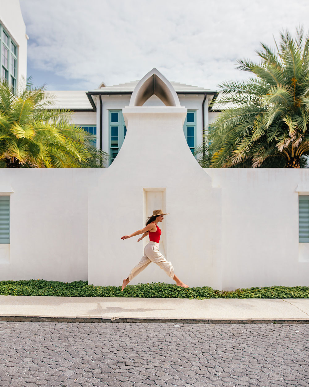 woman jumping for joy in front of wall