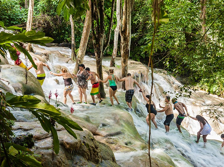 Tourists holding hands and walking up Dunns River Falls