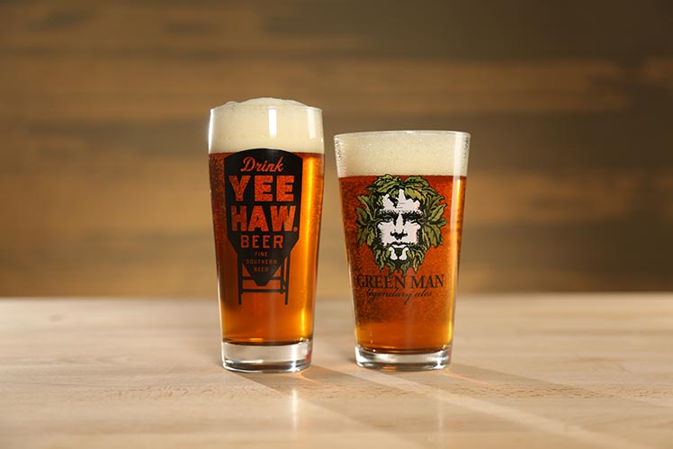 Two glasses of beer displaying Yee-Haw and Green Man Beers
