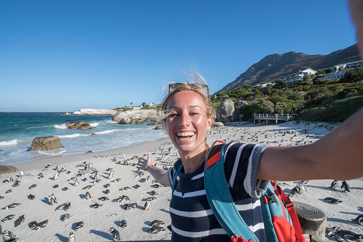 Tourist taking a selfie photo at Bould Beach with penguins in the background