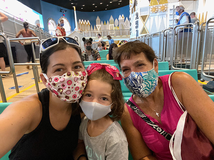 "three family members wearing Covid-19 masks while on ""It's a Small World"" ride at Walt Disney World's Magic Kingdom"