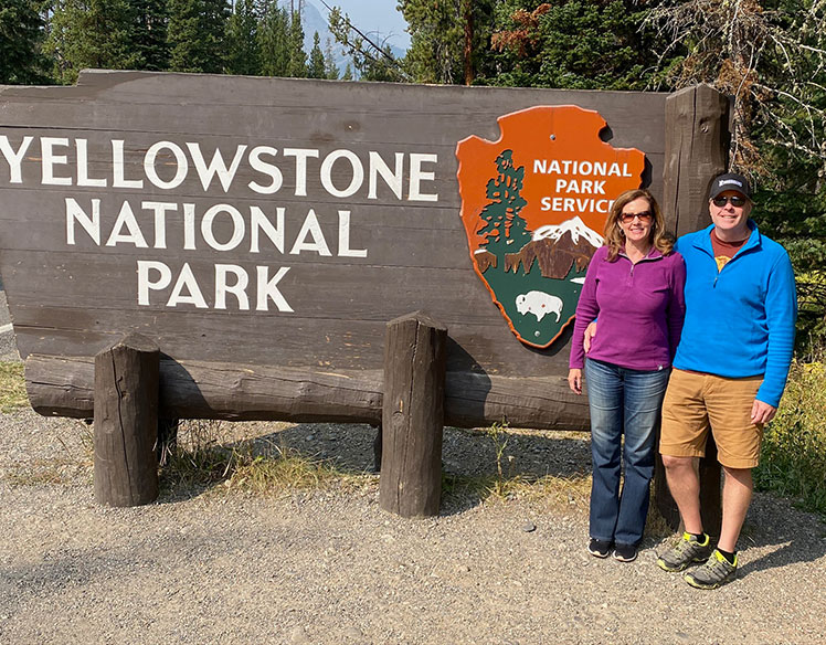 two travelers posing in front of Yellowstone National Park