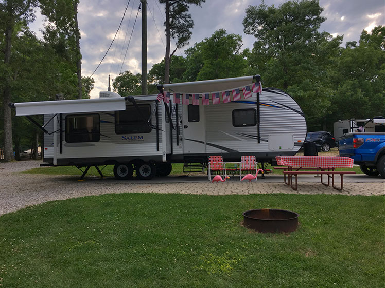 camper parked and decorated with flags and flamingo yard decorations
