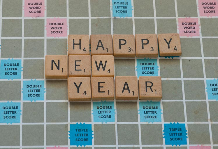 scrabble board with the pieces spelling out Happy New Year