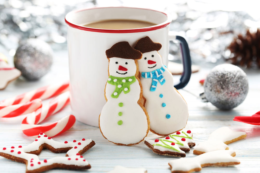 snowman cookies in front of mug of hot chocolate