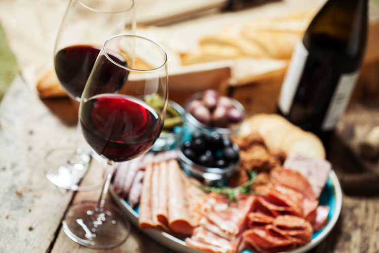 a glass of red wine with a plate of meats and cheeses
