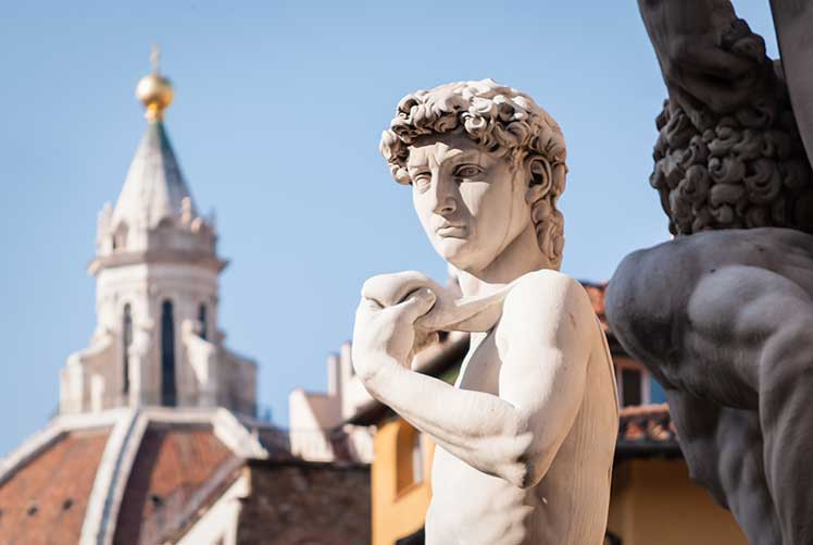 Statue of David with cathedral in the background