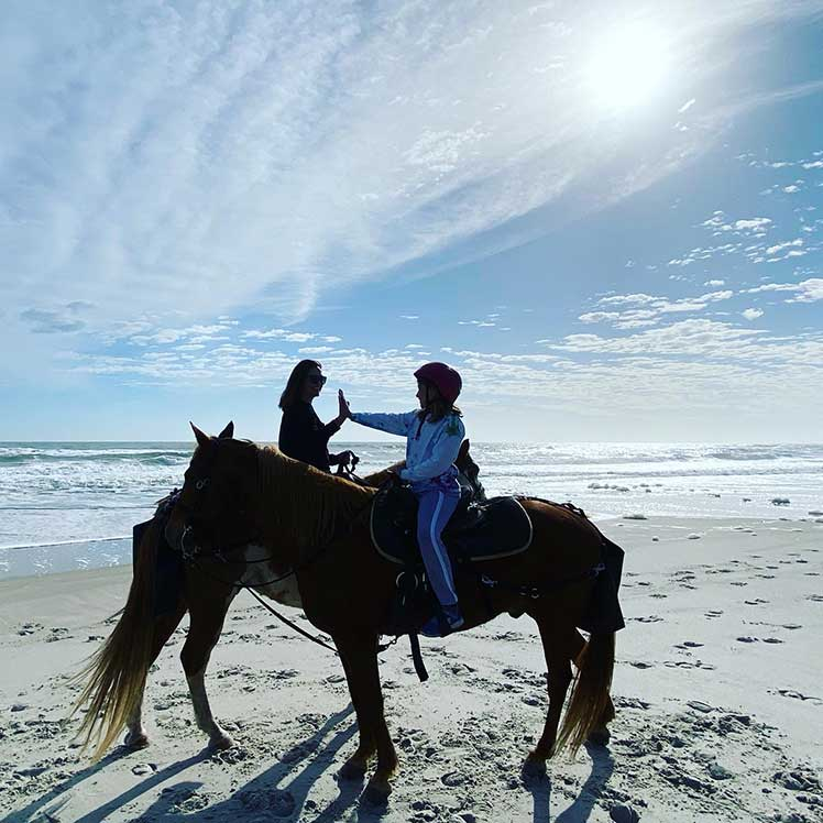 two people horseback riding on the beach