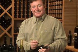 Richard Childress putting an autograph on a bottle of wine from his winery