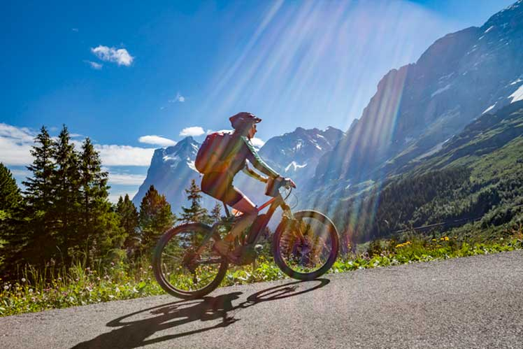 person riding eBike in Switzerland with mountains in the background
