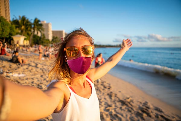 Young woman takes selfie on Waikiki beach in Honolulu, Hawaii, USA