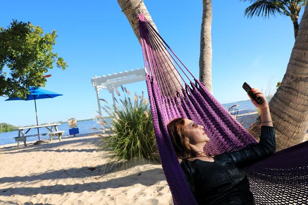 oman taking selfie by using mobile phone and relaxing in hammock on the sandy beach in Key West, Florida