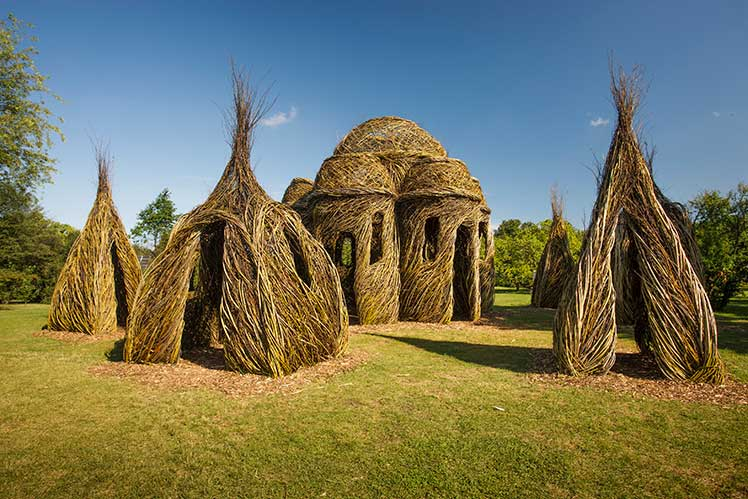 large display of stickwork buildings by Patrick Dougherty