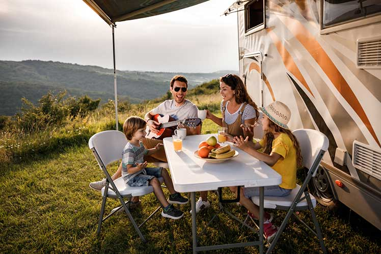 family dinging outside their parked RV in the mountains