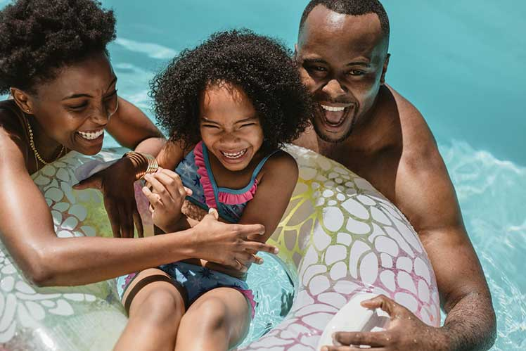 daughter, mother and father in pool