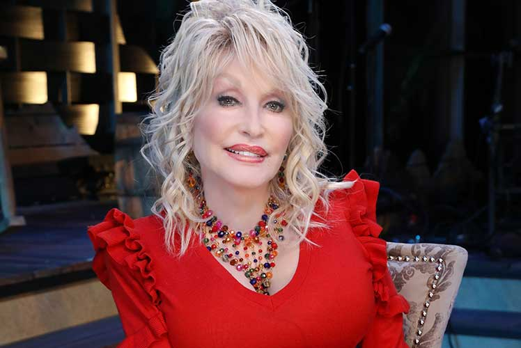 Dolly Parton sitting in a chair wearing a red top