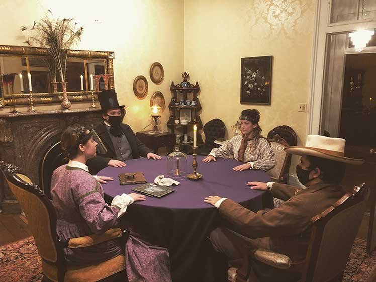 people sitting around a table for a Victorian seance