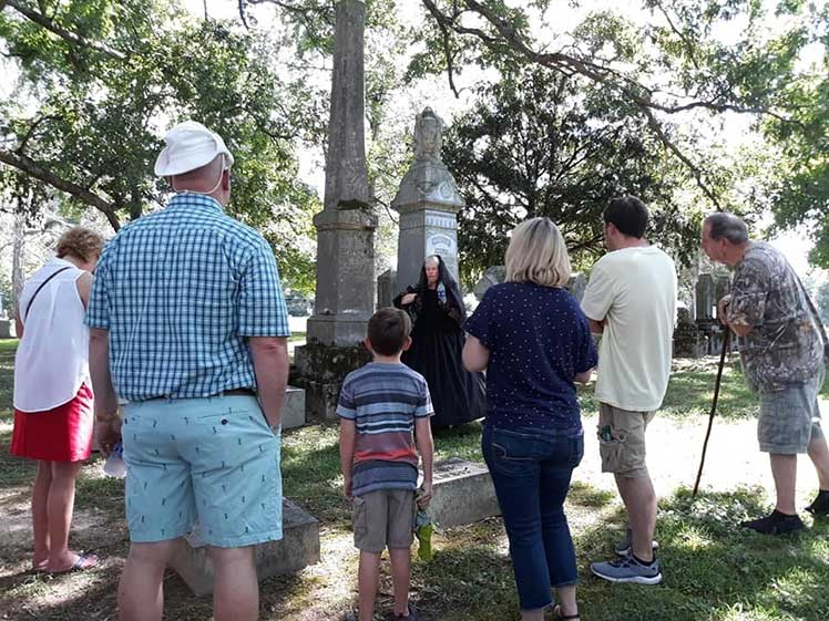 people on a tour of a cemetery