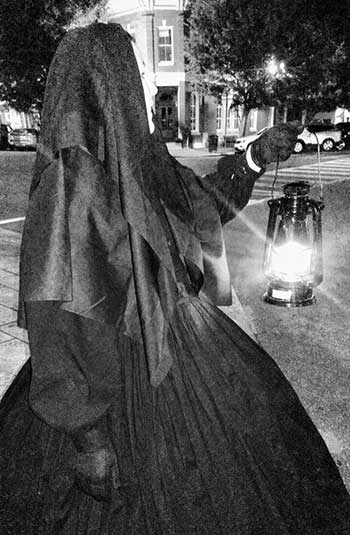 black and white photo of a woman walking with a lantern on a downtown street